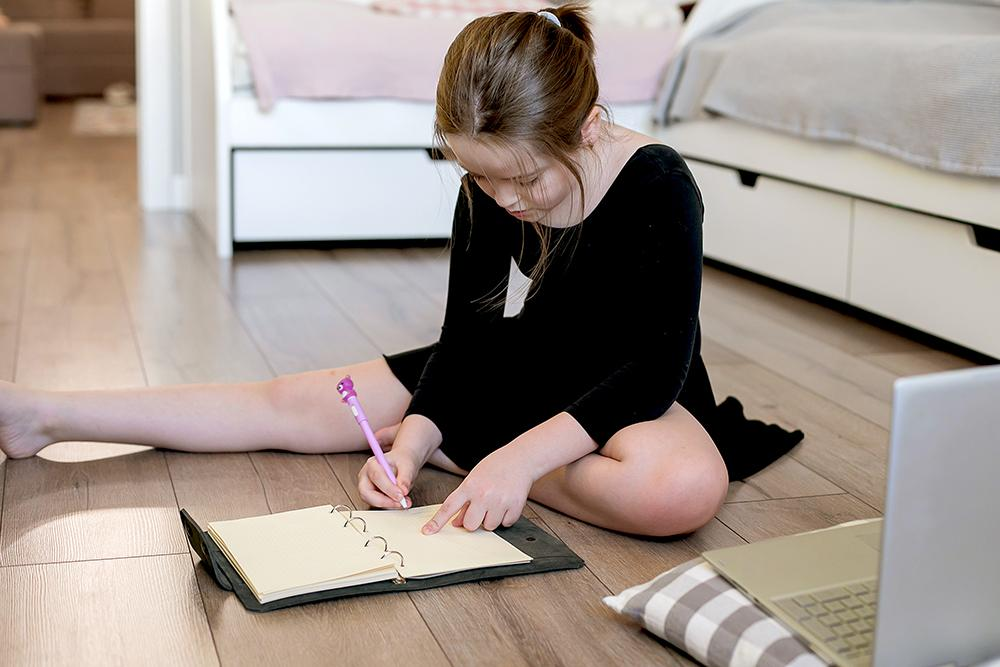 Young white ballerina sitting on floor and writing in a notebook.