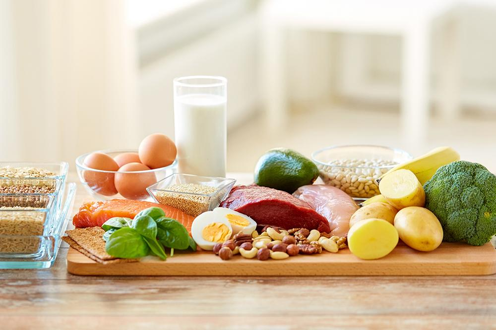 Table full of foods that provide protein, including eggs, meat, and vegetables.