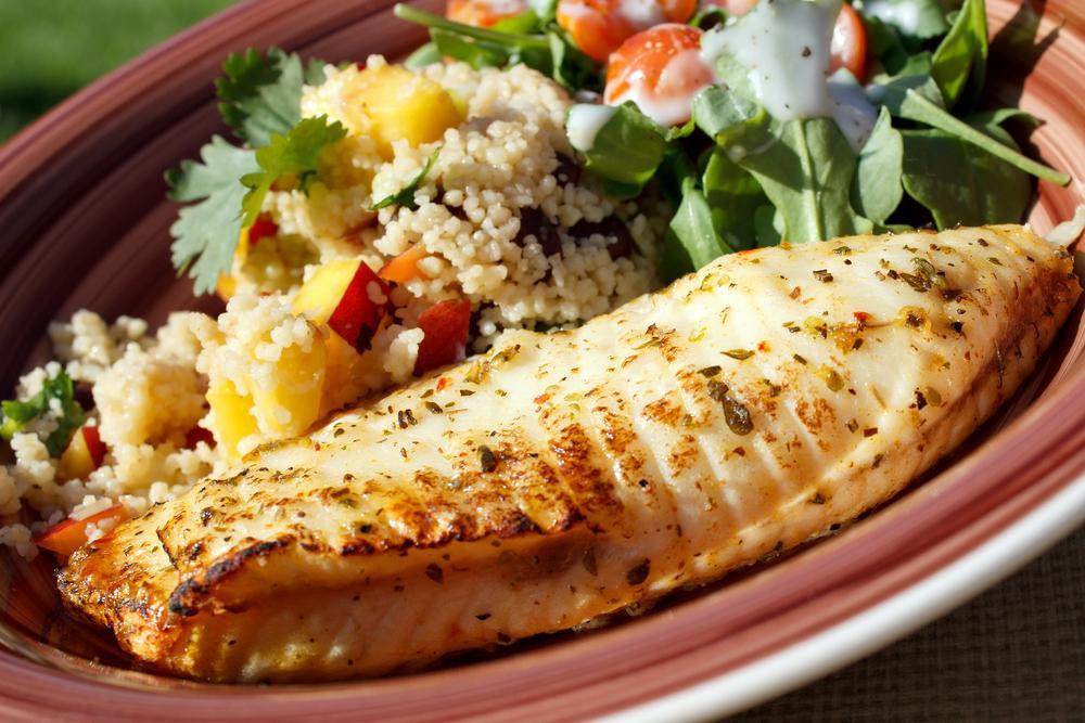Grilled tilapia next to vegetable quinoa.