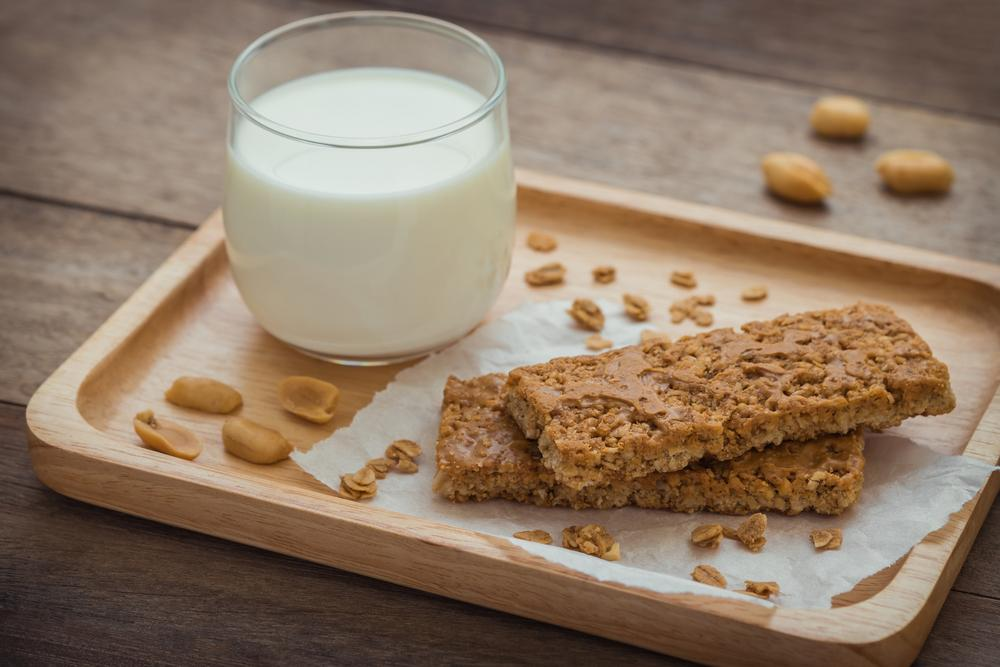 Granola bar next to a glass of milk.