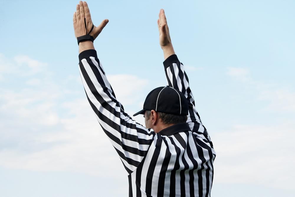 Referee with hands in air.