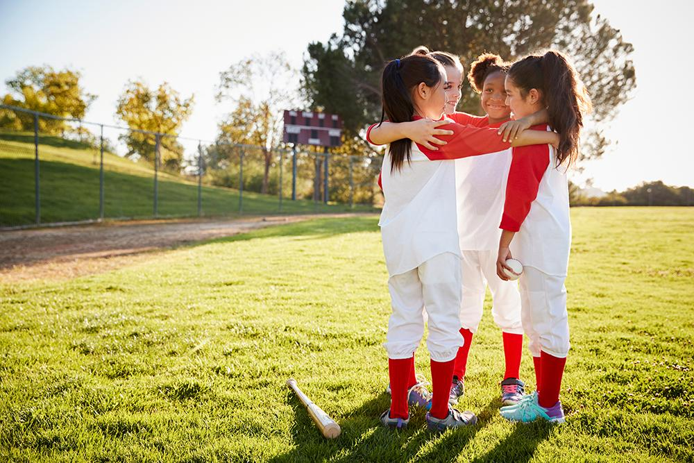 Diverse young girls in a huddle on softball field.