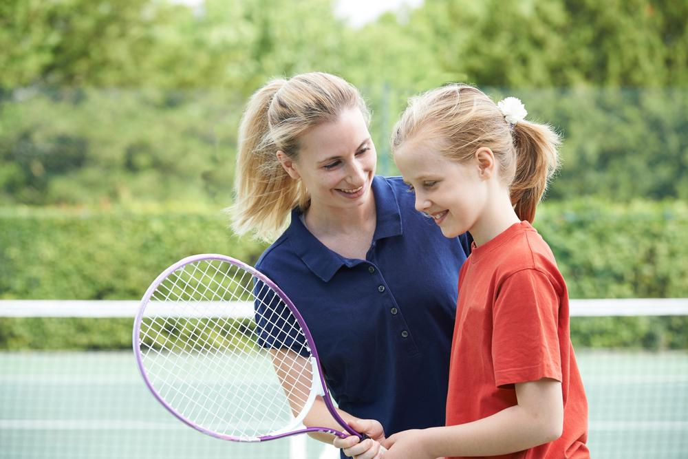Woman coach talking to young female tennis athlete.