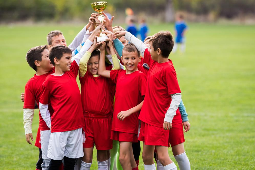 Young male soccer team holding a trophy together.
