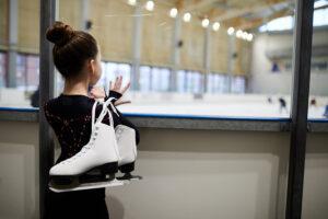 White girl looking at skating rink while holding figure skating skates.