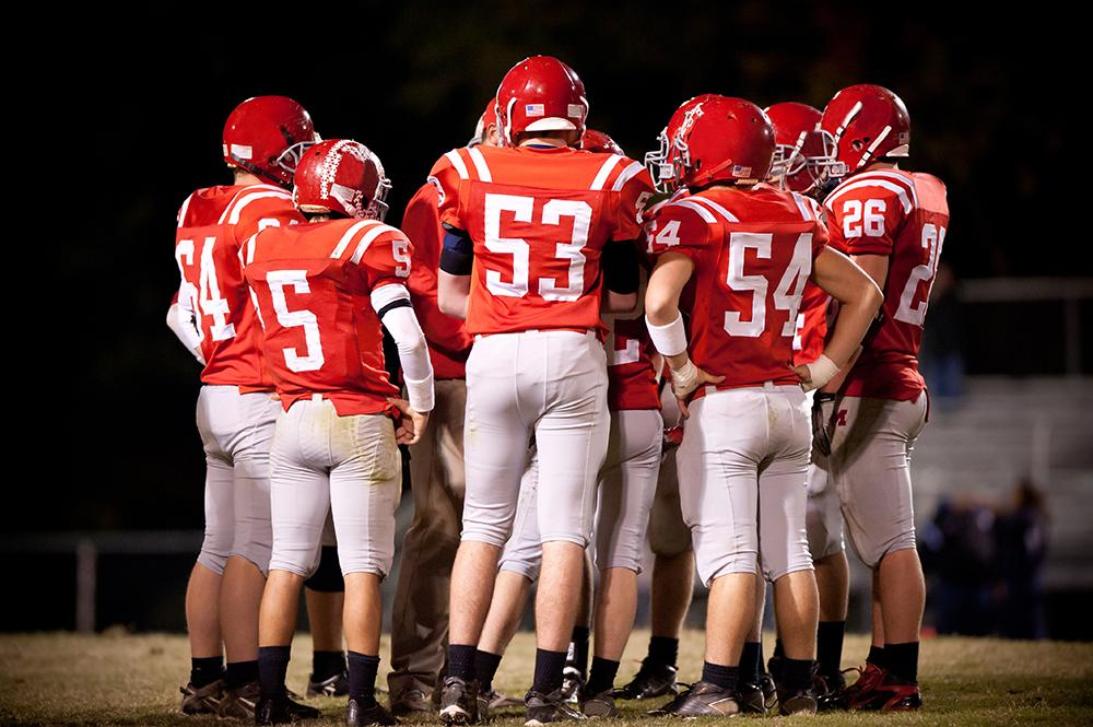 Football team huddled on field during night game.