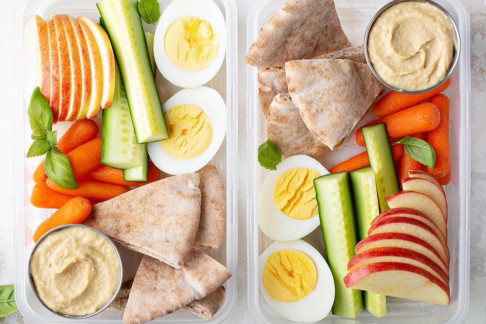Two tupperware containers filled with veggies, hard boiled eggs, pita, hummus, and sliced apples.