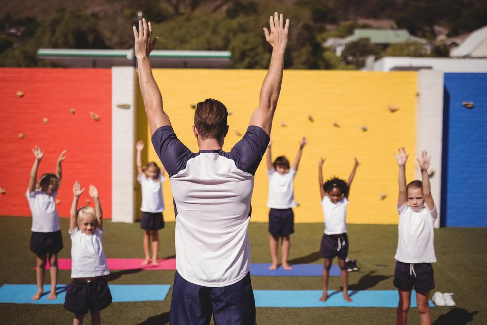 Man leading children in a yoga class outdoors.