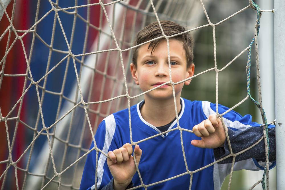Young boy looking out through soccer net.