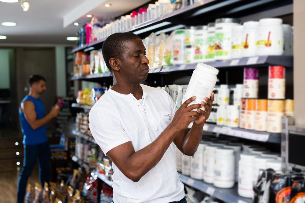 Man examining a large supplement bottle in a store.