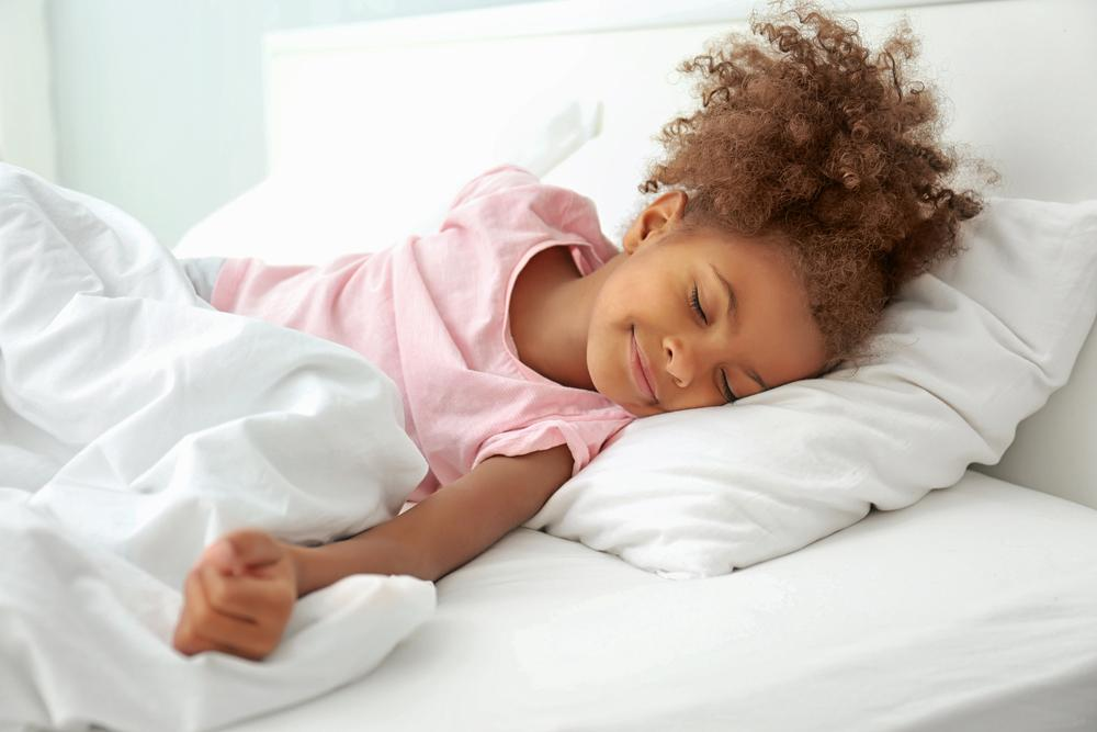 Young black girl happily sleeping.