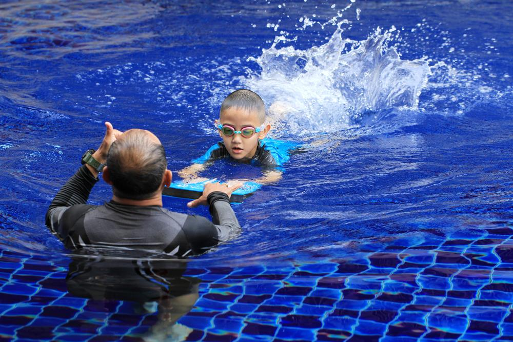 Young boy being coached with a kickboard in a pool.