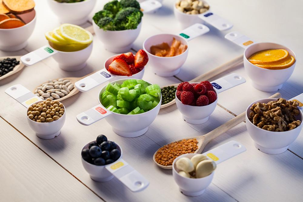 Measuring cups fullf of different fruits, nuts and veggies.