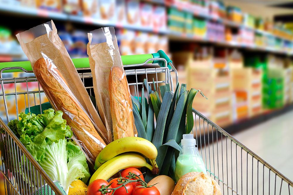 Shopping cart full of bread, fruits and vegetables.