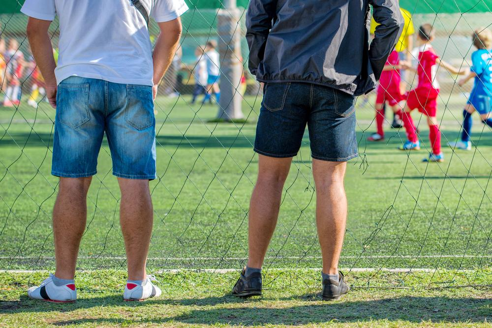 Rear view of two dads on sidelines at youth sports game.
