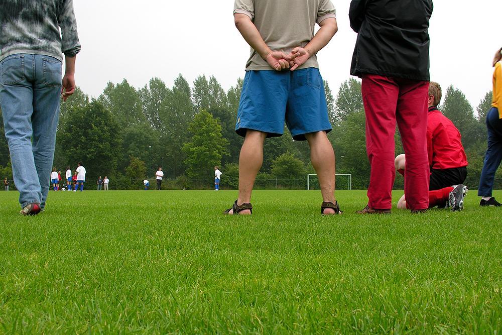 Parents standin on sideline at soccer game.