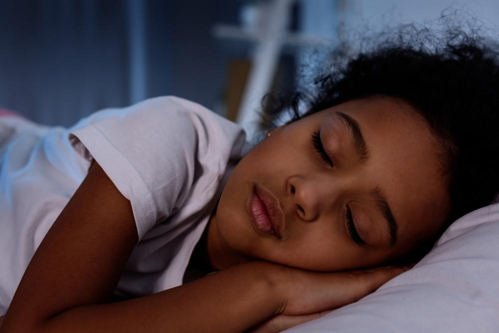 Young black girl asleep in bed.