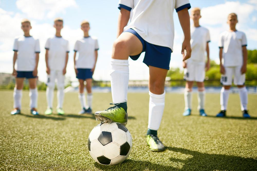 Captain of soccer team viewed from waist down standing in front of other team members.