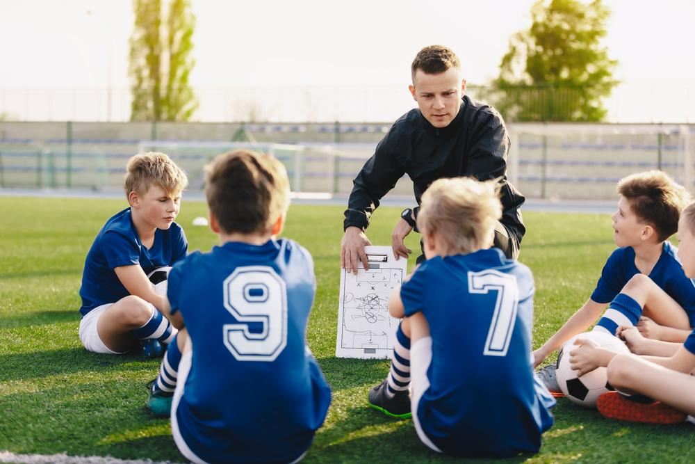 Male coach sharing game plan with young male soccer team.