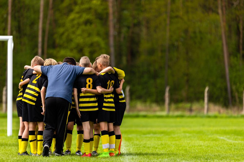 Young male soccer team huddling with coach.