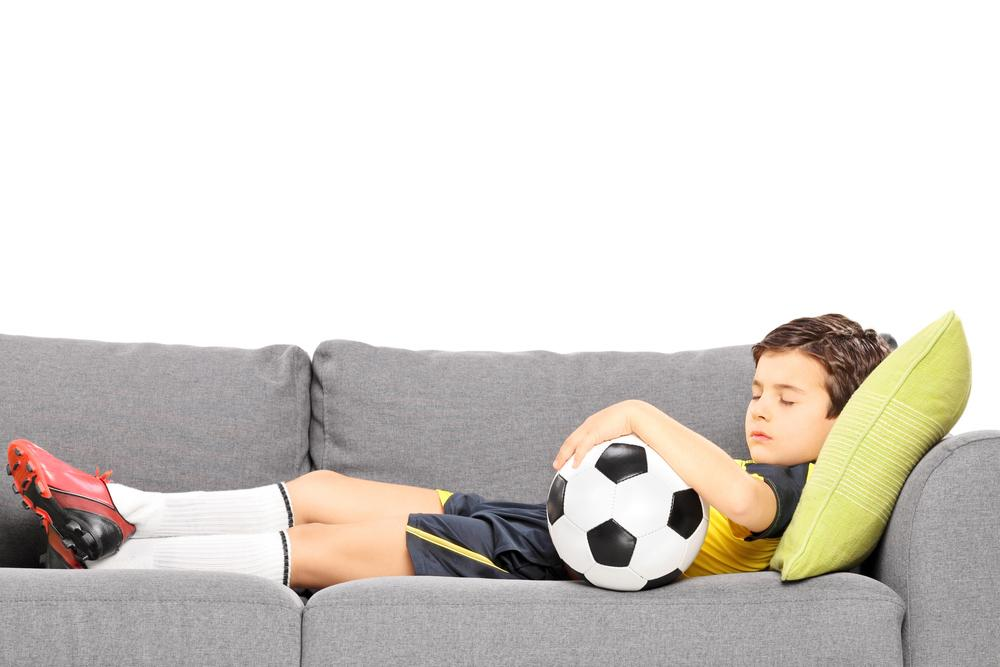 Boy in soccer outfit with ball sleeping on couch.