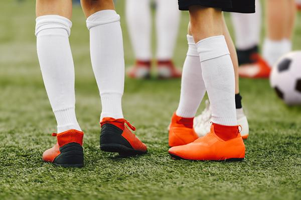 Close up of the tall socks worn by two young soccer players.