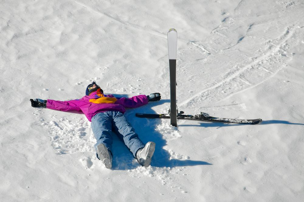 Young skiier laying in the snow.