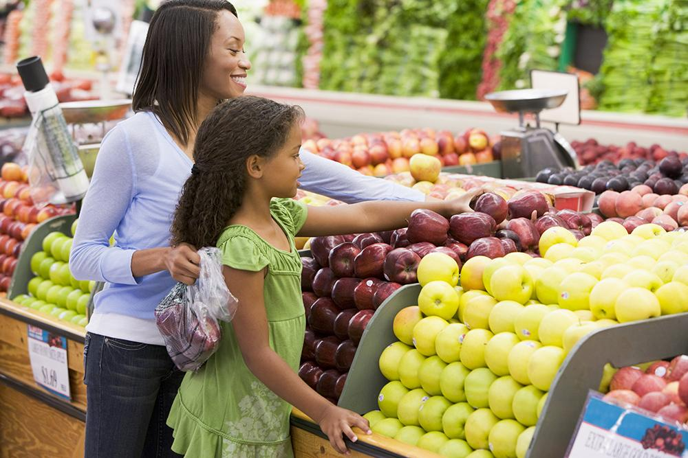 Black mom helping daughter grab apple at a grocery store.
