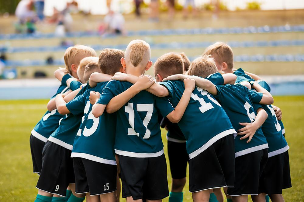 Young male kids in a huddle before a sports game.