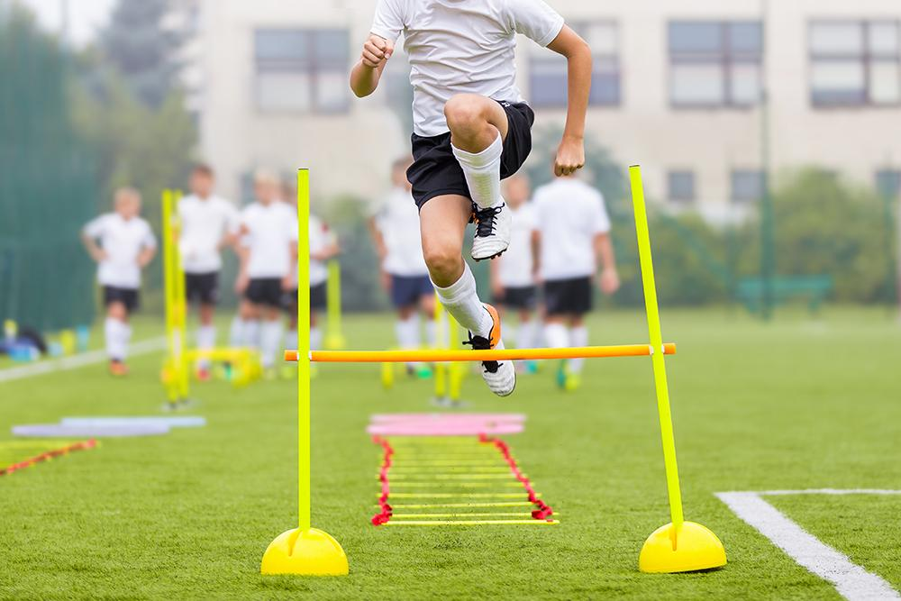 Teen male training by jumping over hurdle.