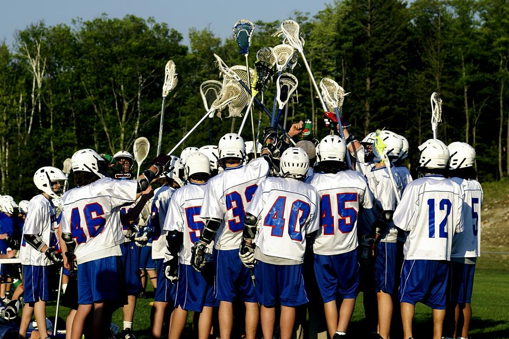 Lacrosse team huddled with sticks in the air.