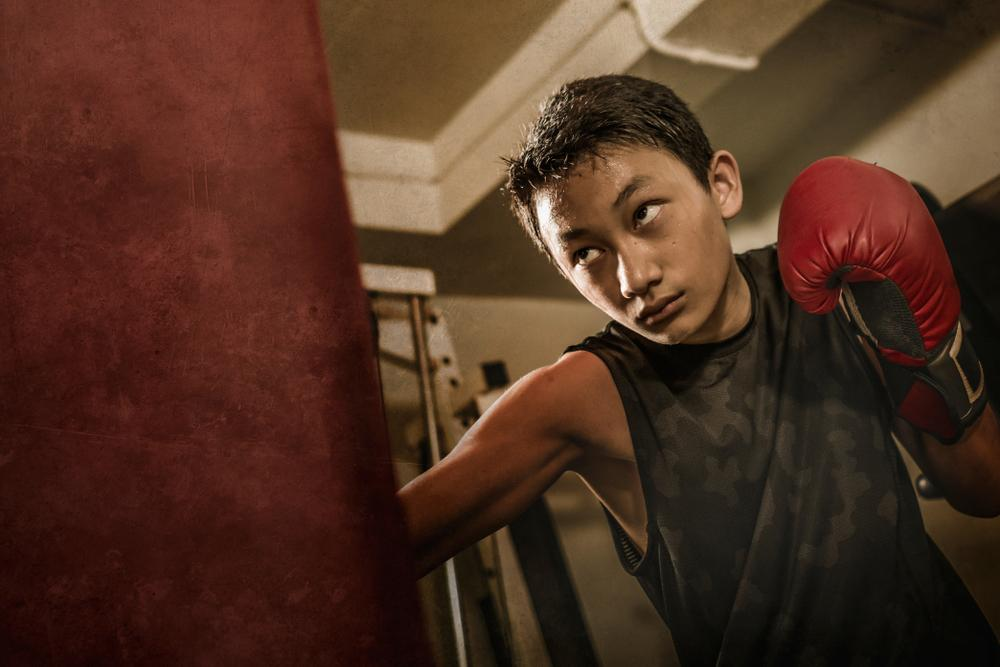 Young boy boxing and sweating.