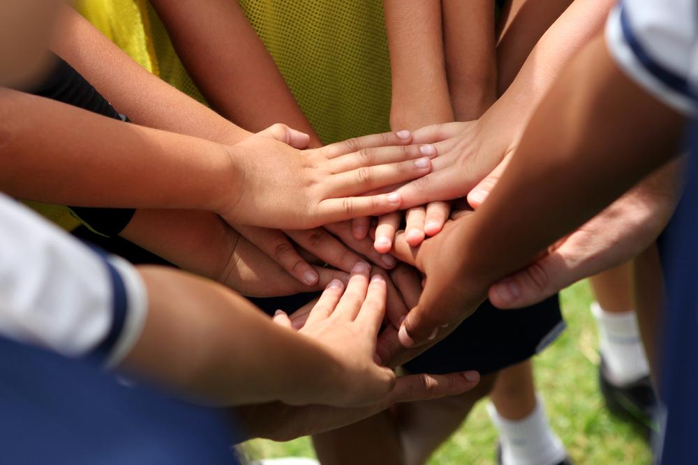 Close up of kids hand together in a huddle.