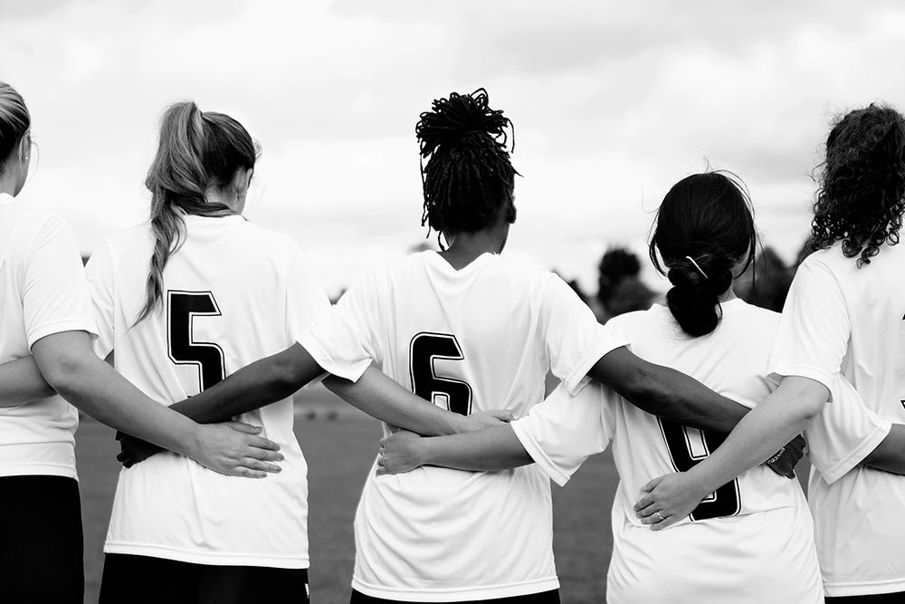 Diverse teen girl sports team linking arms.