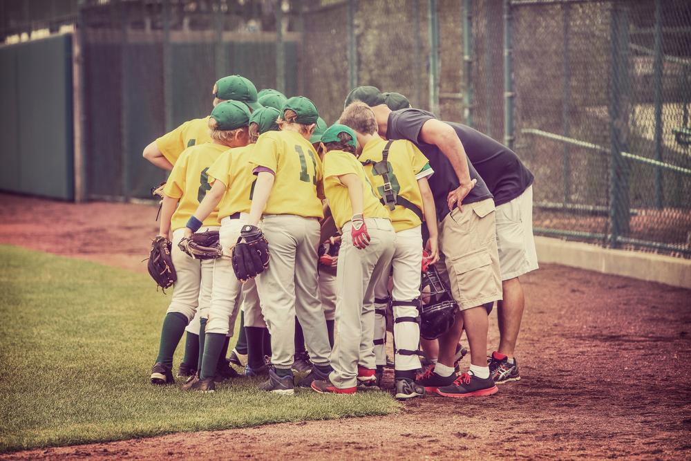 Young baseball team with coach in a huddle.