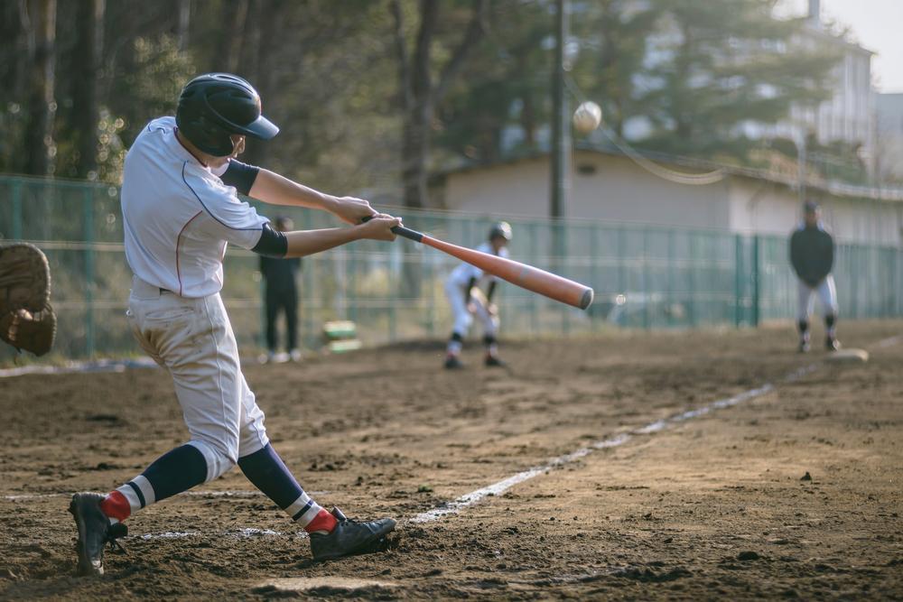 Teen hitting baseball during game.