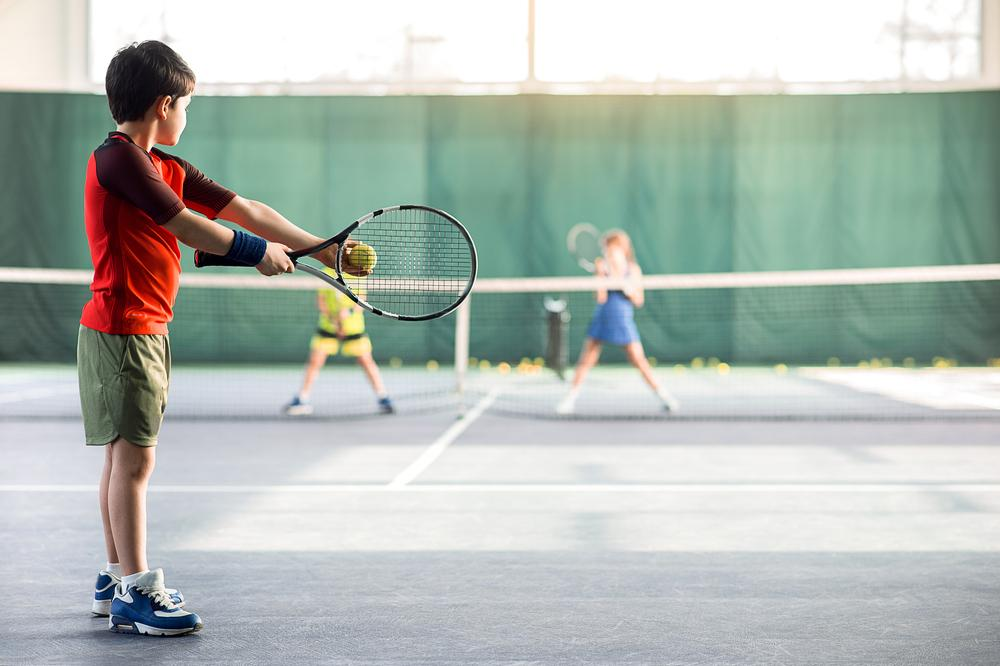 Young boy about to serve in tennis.