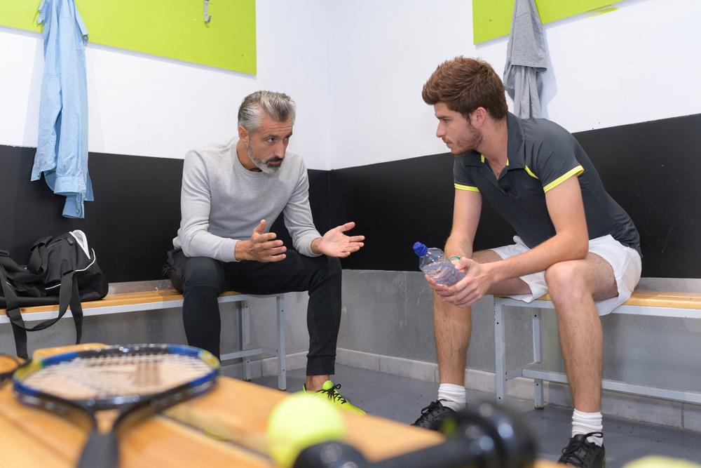 Tennis coach talking to young male athlete in locker room.