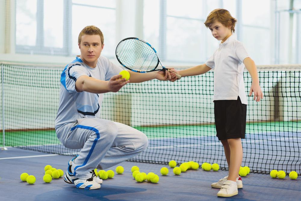 Tennis coach training with young male athlete.