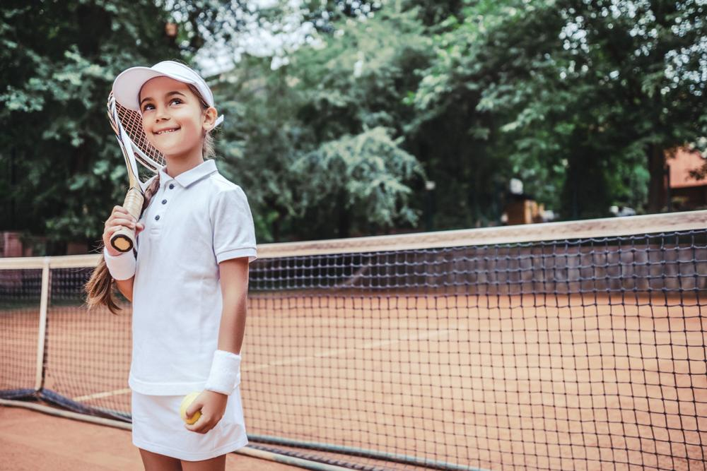 Little girl smiling on a tennis court in tennis gear, holding a racket.