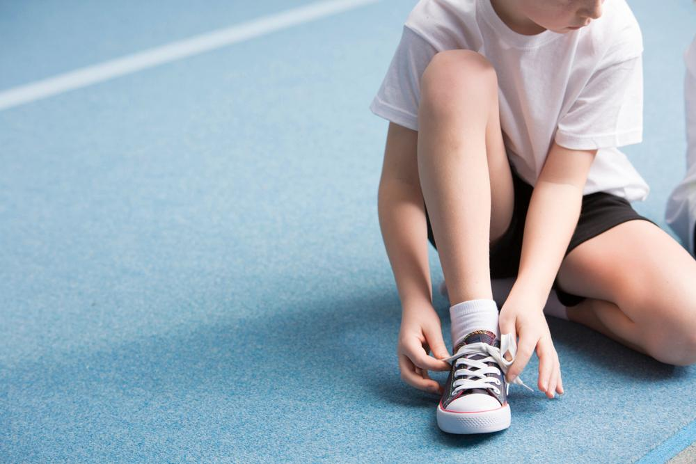 Young boy tying his shoe.