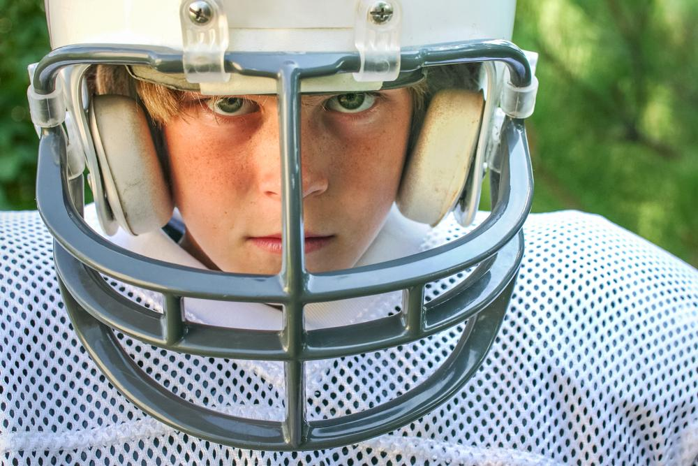Close up image of a young boy football player.
