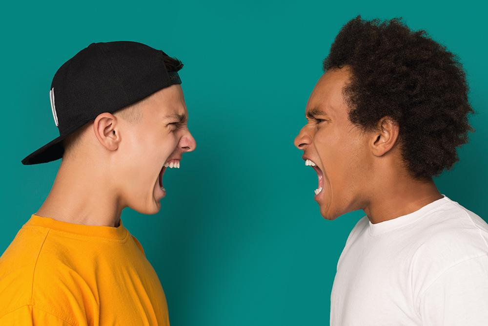 Two teen boys yelling angrily at each other.
