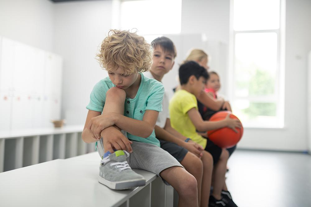 Young white boy sitting next to other boys on a locker room bench looking sad.