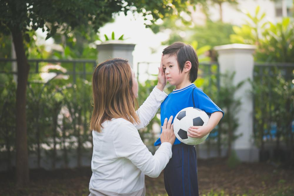 Mother kneeling to comfort young son holding soccer ball.