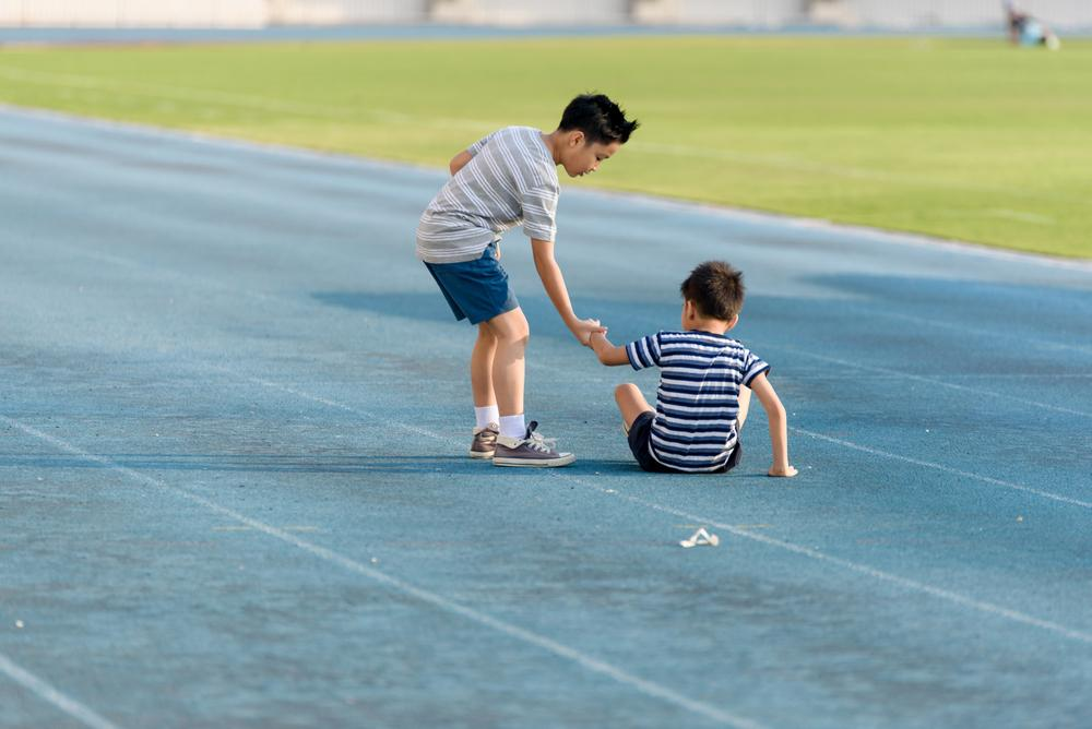 Young boy helping another younger boy stand up on a track.
