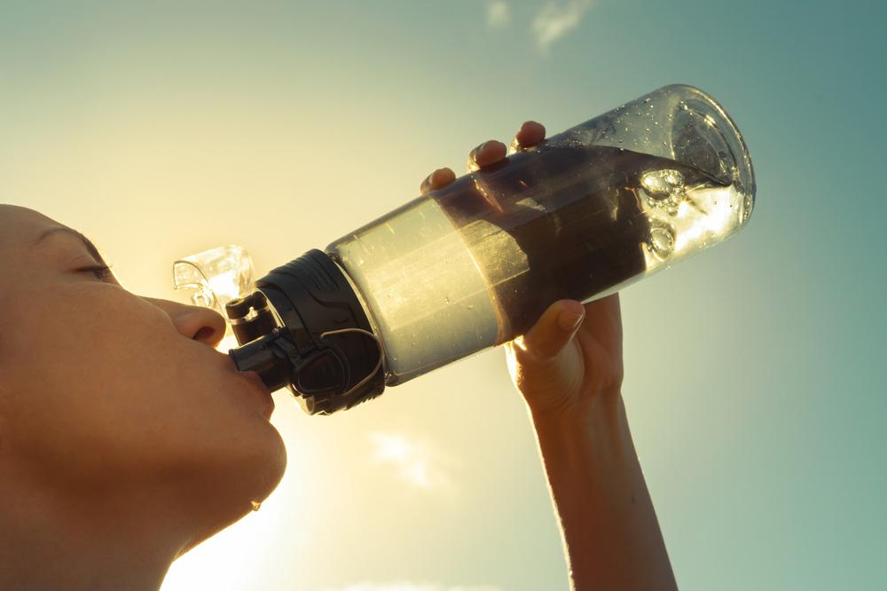 Close up of young woman drinking water out of reusable bottle.