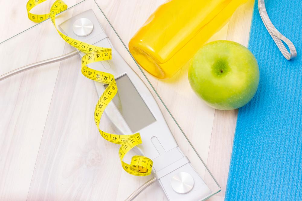 A scale next to a measuring tape, water bottle, and apple.