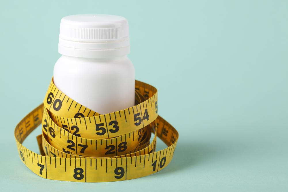 Tape measure around a white pill bottle.
