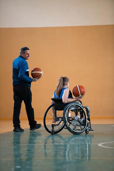 Coach with younger female wheelchair basketball player.